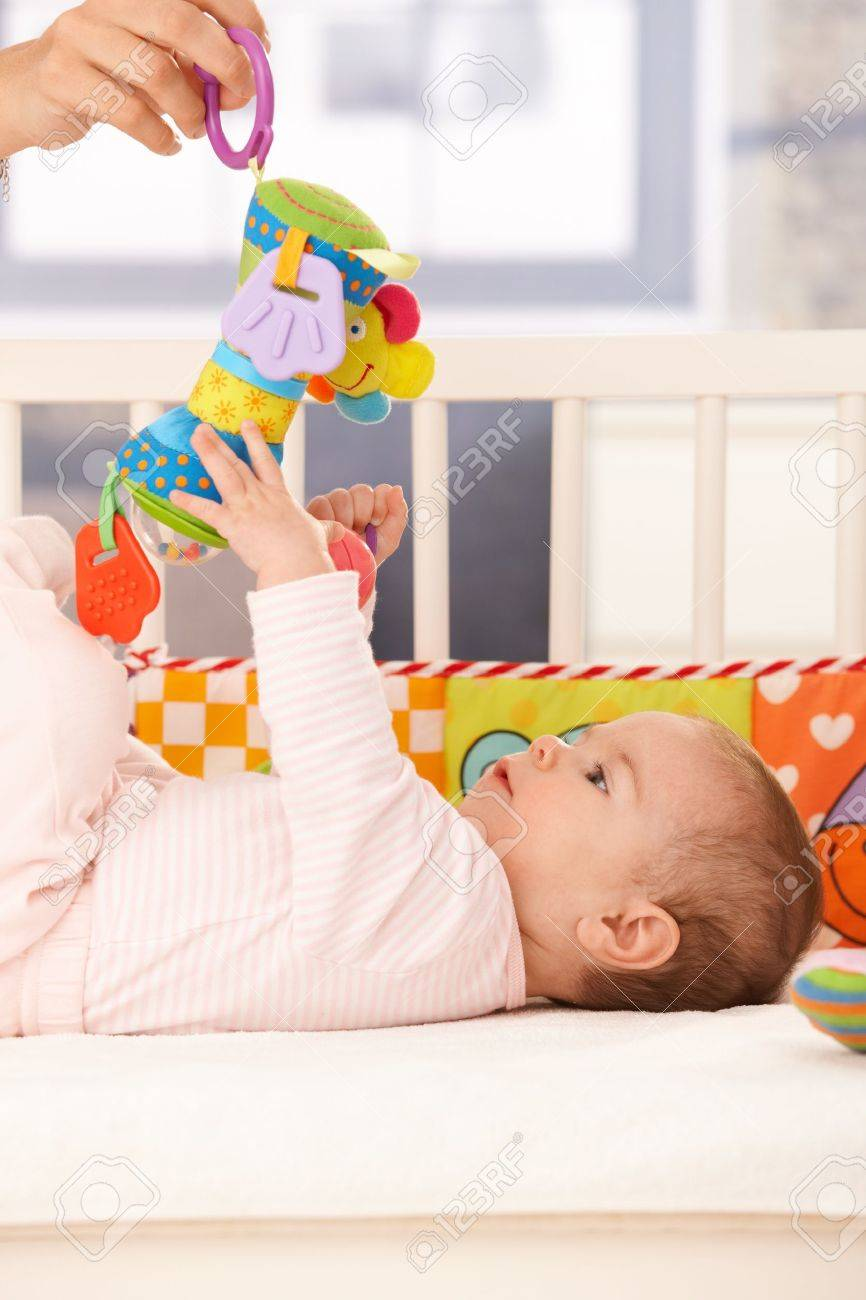 Baby girl playing, mother holding infant toy to reach. Stock Photo - 8747400