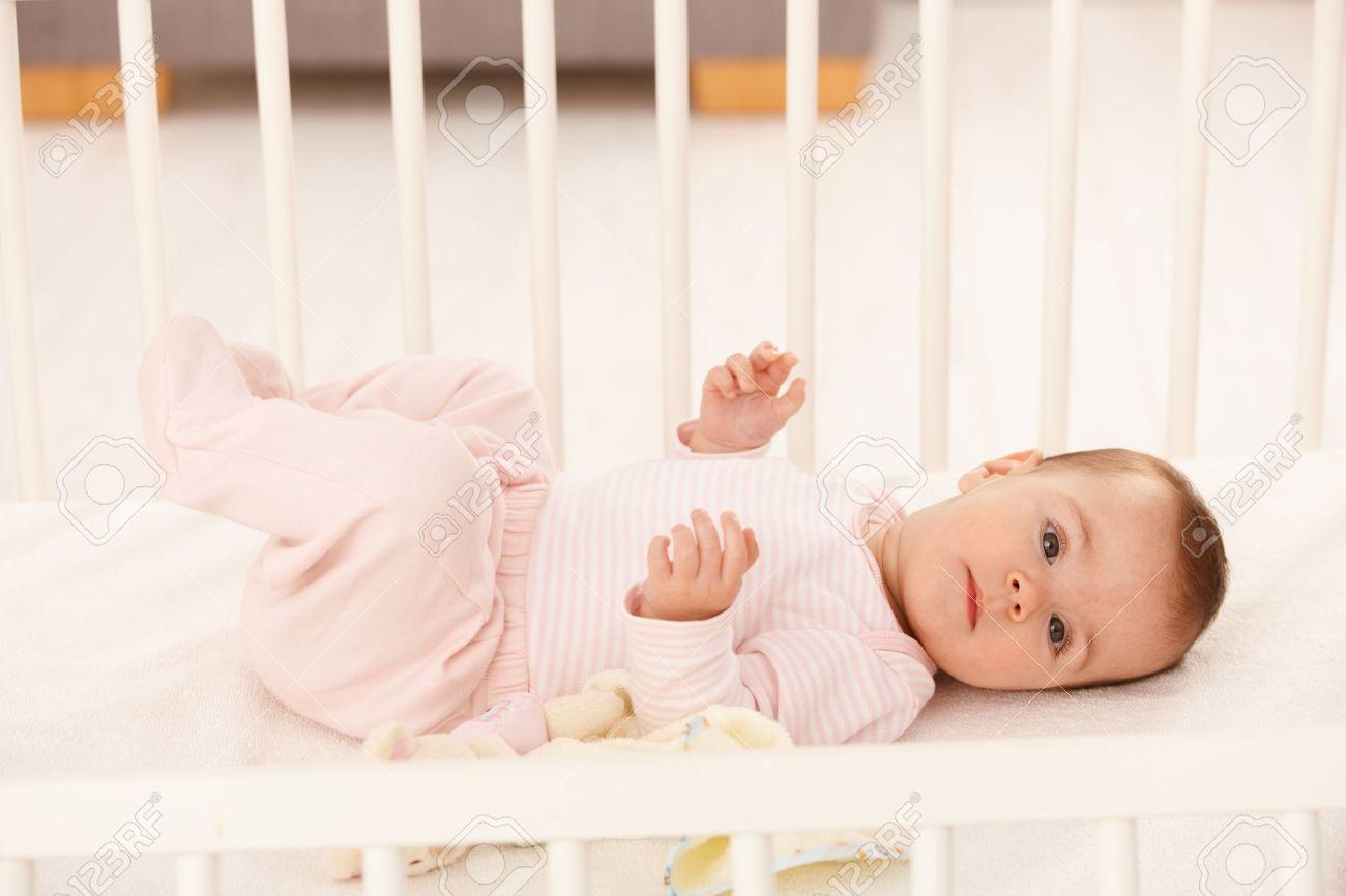 Beautiful infant girl in cute pink dress lying in crib. Stock Photo - 8747377