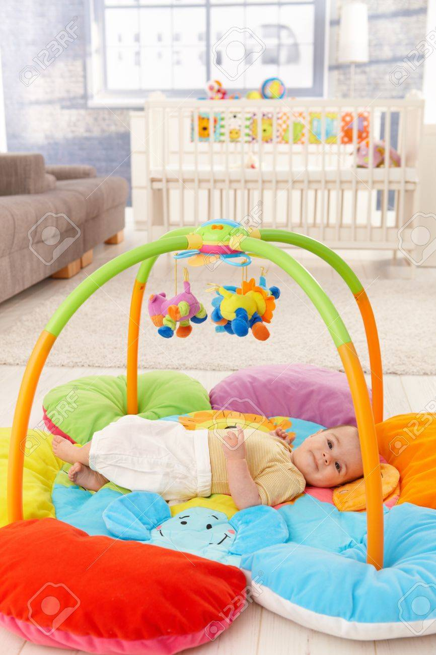 Happy baby girl smiling on playmat. Stock Photo - 8747433