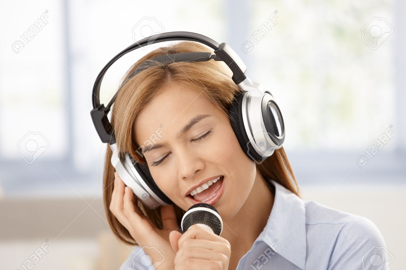 Young attractive female singing with joy, using microphone and headphones, smiling. Stock Photo - 8747515