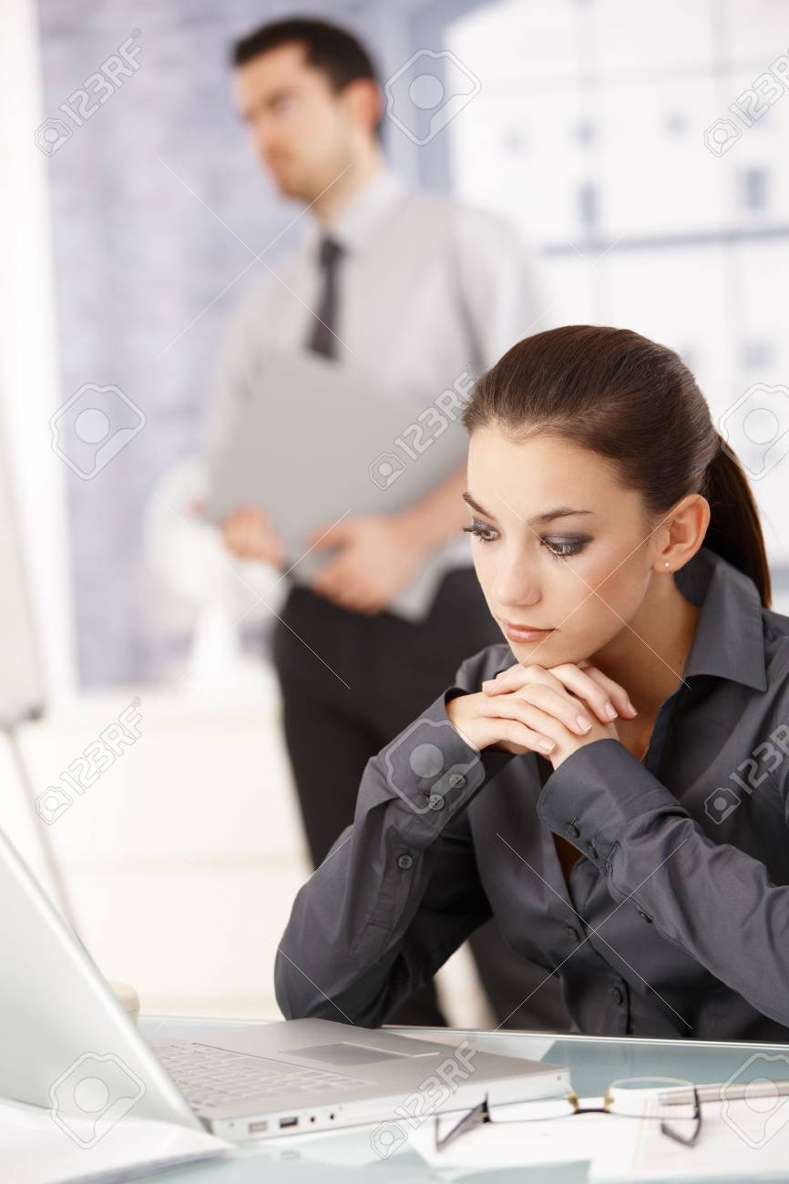 Young attractive woman sitting in office at desk, looking at laptop, man standing in background. Stock Photo - 8747494