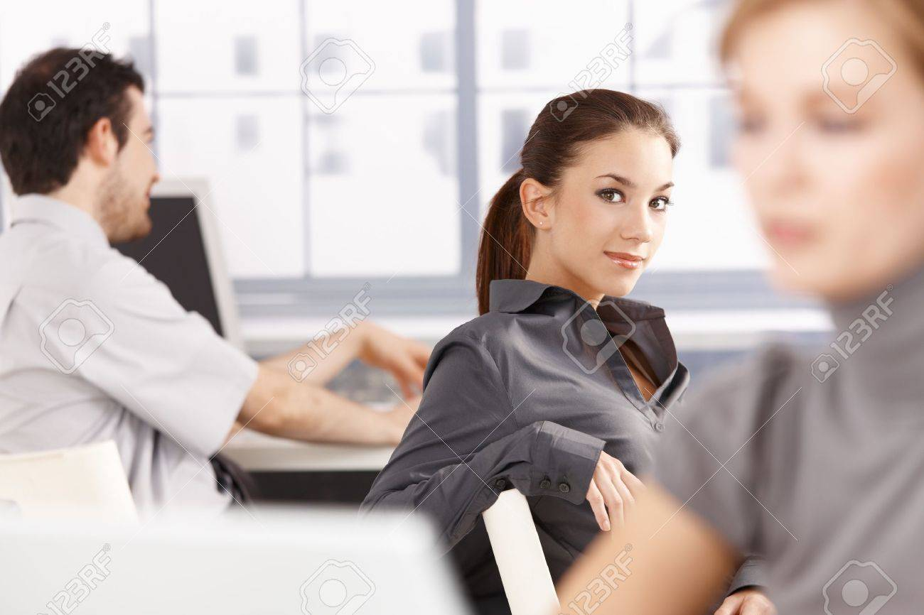 Young people sitting at desk, working in office, smiling. Stock Photo - 8747498