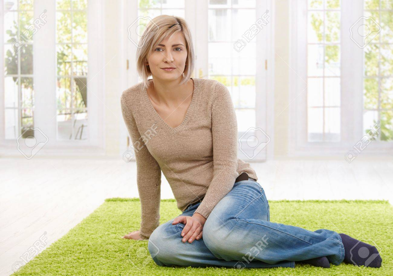 Portrait of attractive young blond woman sitting on floor at home looking at camera, smiling. Copy space for text. Stock Photo - 8747926