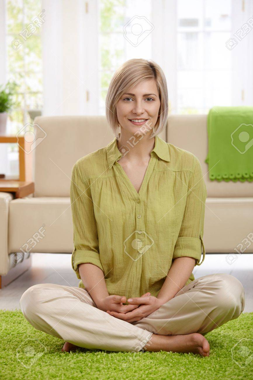 Happy  woman sitting with legs crossed on living room floor, looking at camera. Stock Photo - 8747922