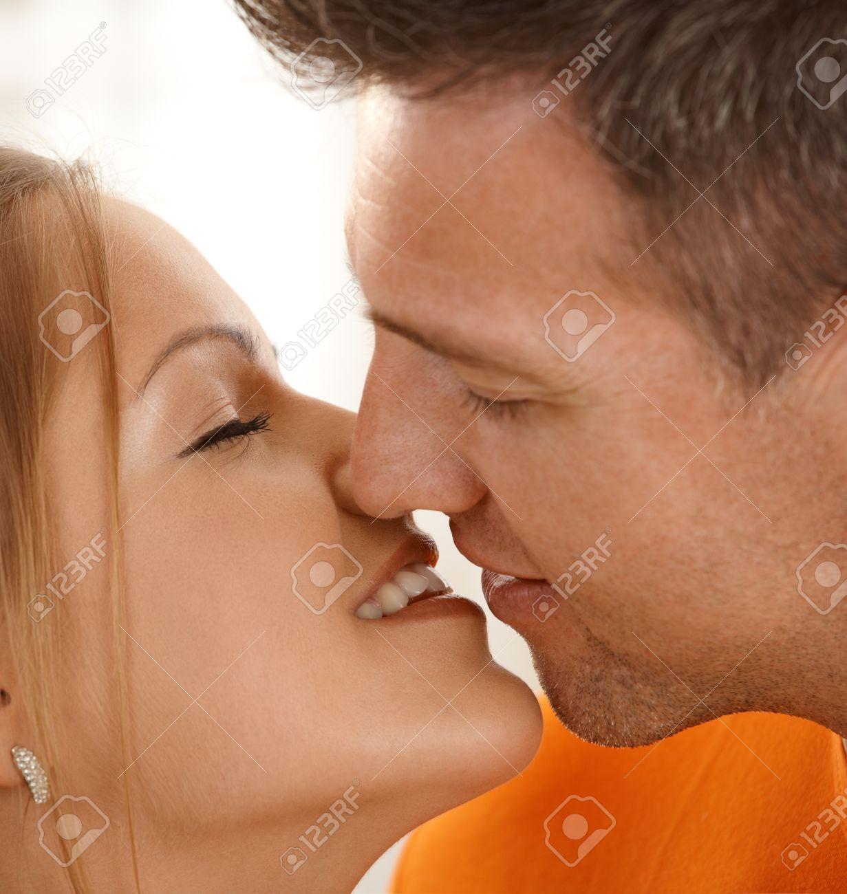 Man kissing smiling woman in closeup, eyes closed. Stock Photo - 8747725