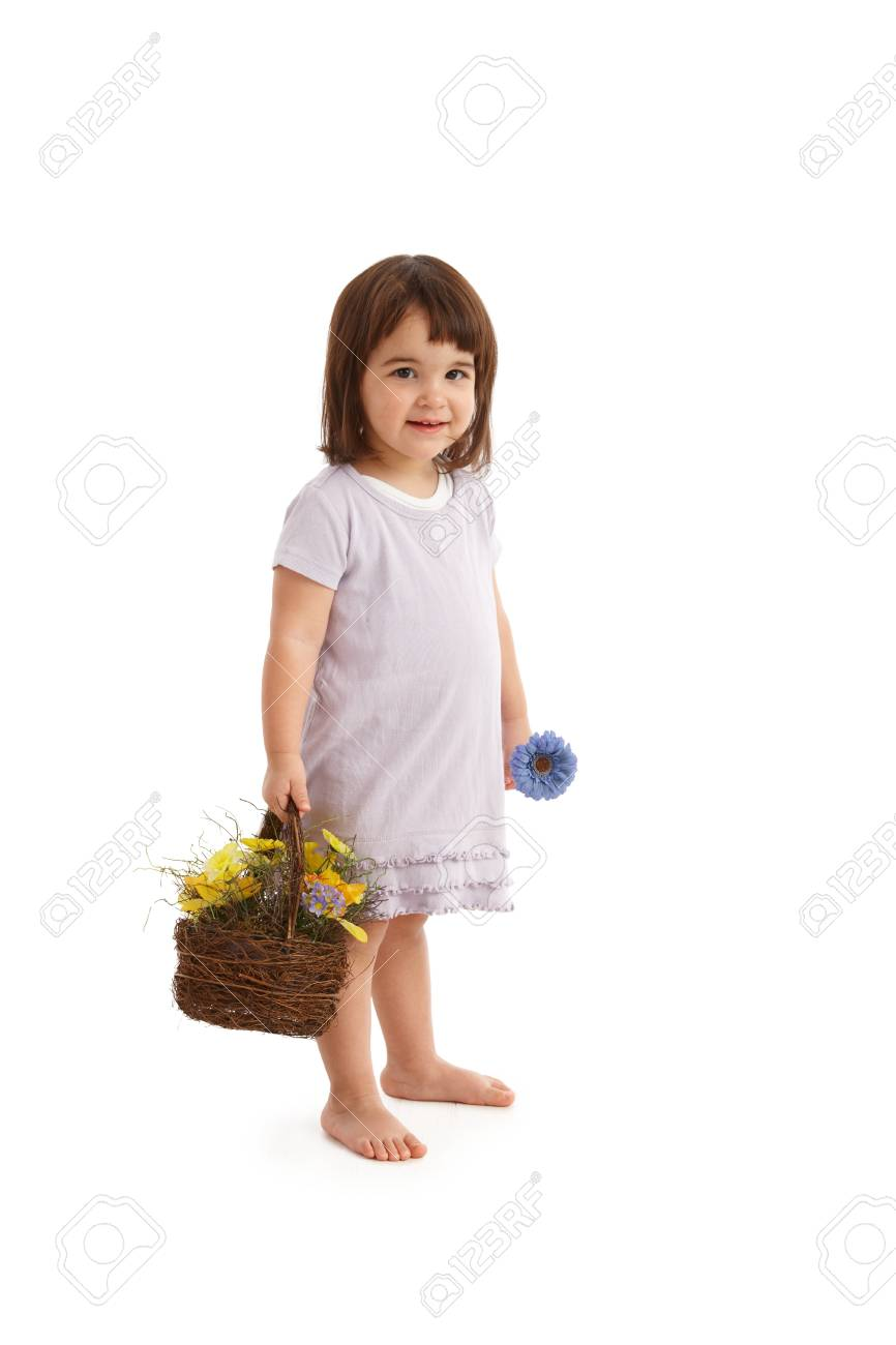Sweet girl with basket full of spring flowers, smiling at camera. Stock Photo - 8747673