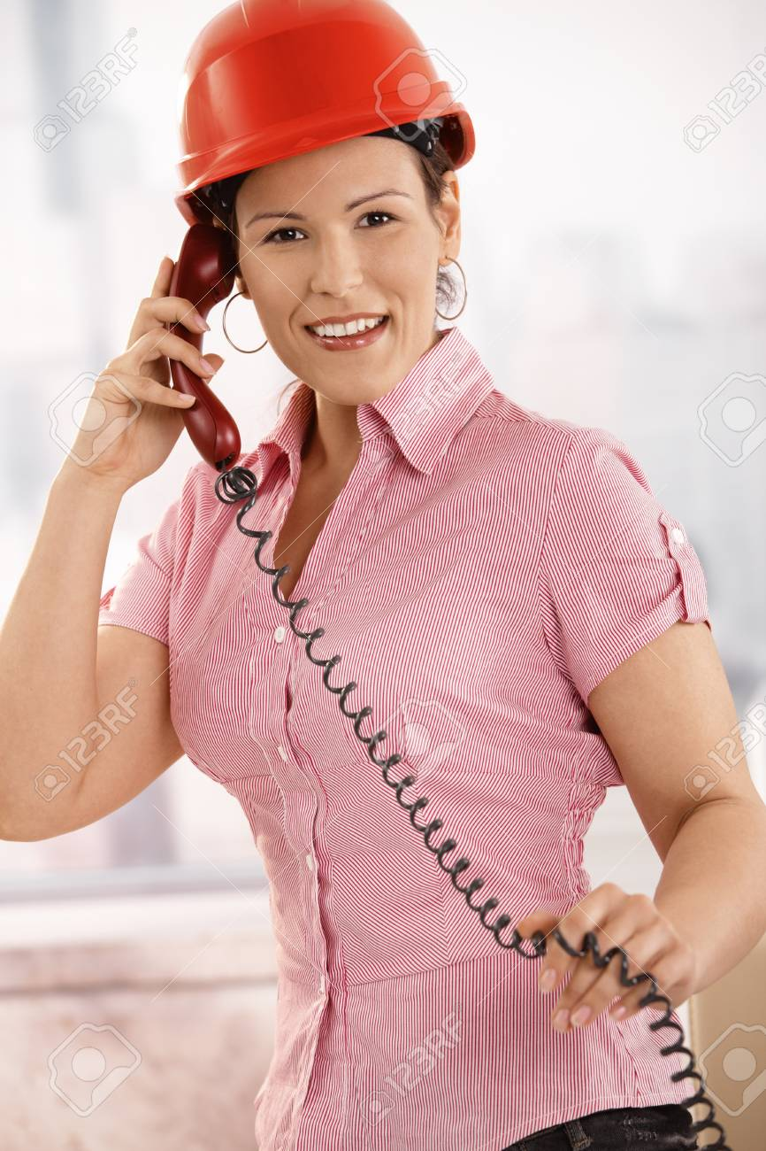 Portrait of female architect talking on landline phone in office, looking at camera, smiling. Stock Photo - 8748788
