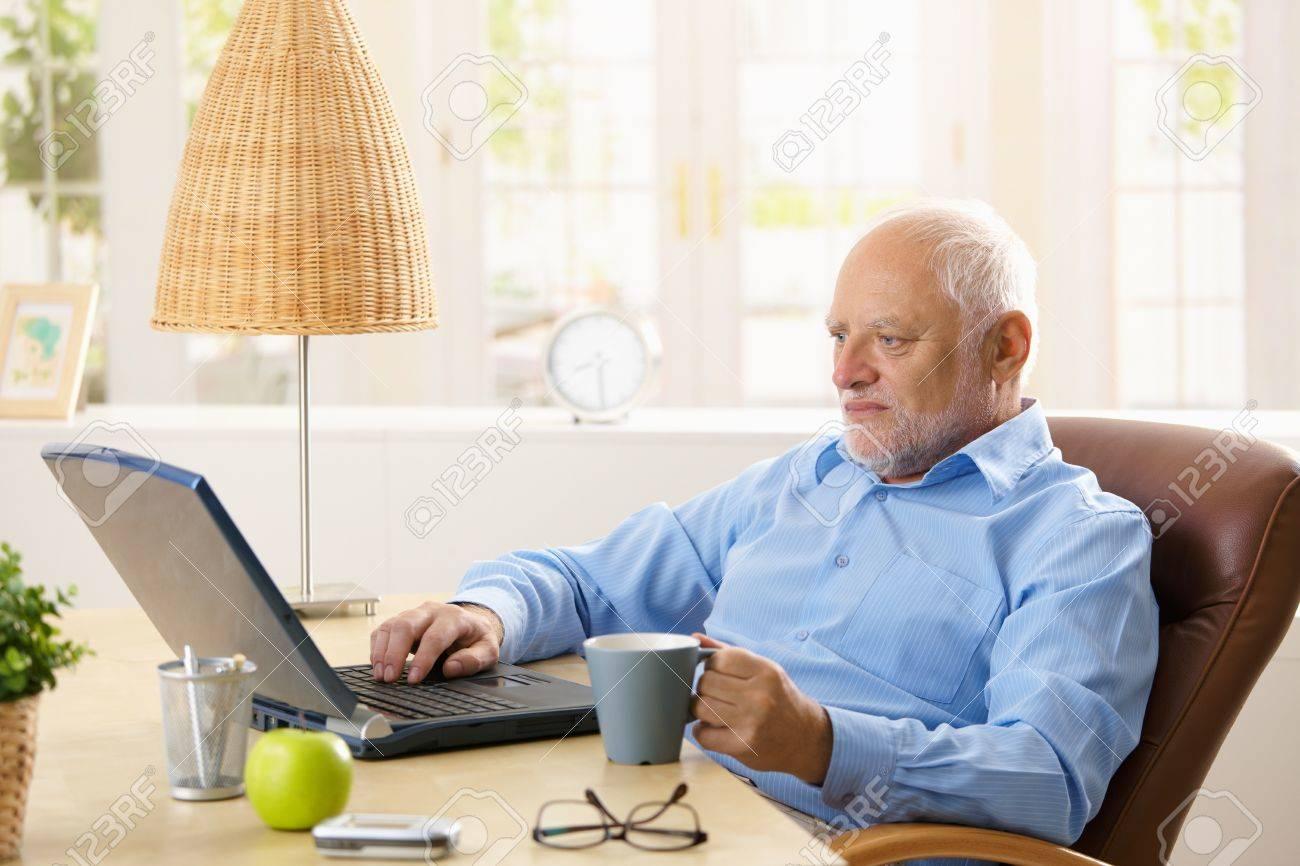 8748717-Elderly-man-using-laptop-compute
