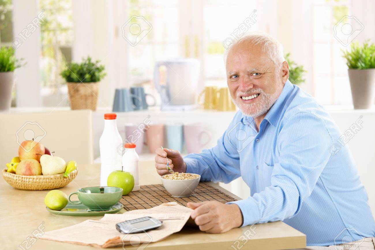 Cheerful healthy senior man having cereal for breakfast in kitchen, smiling at camera. Stock Photo - 8748113