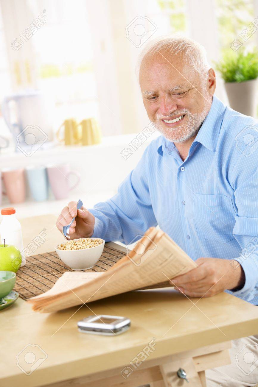 Smiling senior man sitting in kitchen reading papers while having cereal for breakfast. Stock Photo - 8748120