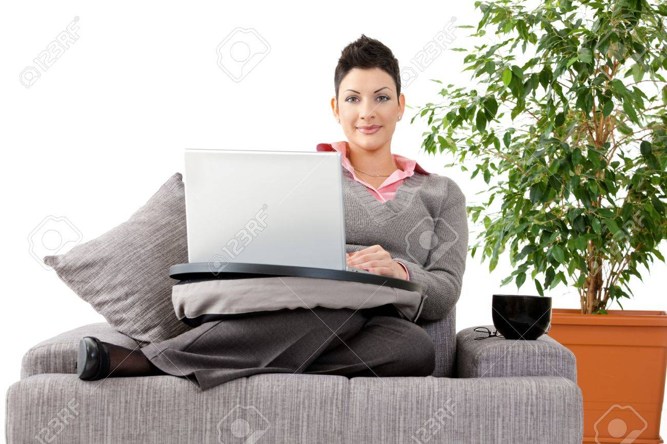 Young woman sitting on couch working on laptop computer at home, smiling. White background with green plant. Stock Photo - 8752493