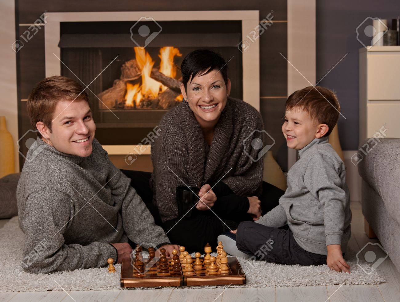 Happy family playing chess at home in a cold winter day, looking at camera, smiling. Stock Photo - 8752509