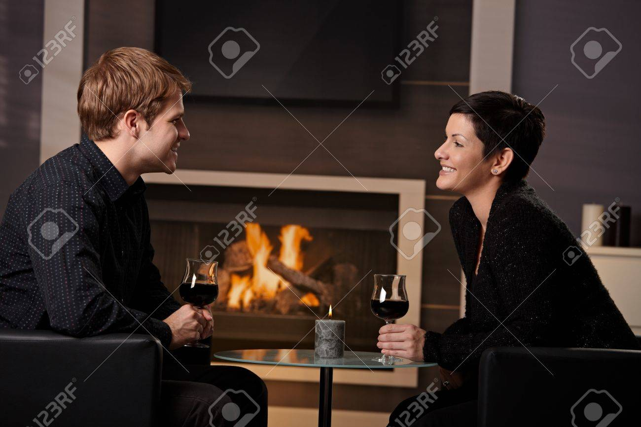 Young romantic couple dating, sitting in front of fireplace at home, drinking red wine. Stock Photo - 8752504