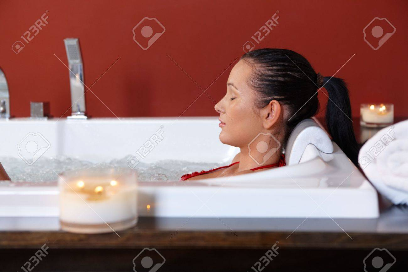 Young woman enjoying wellness bubble bath with eyes closed in candle light. Stock Photo - 8753403