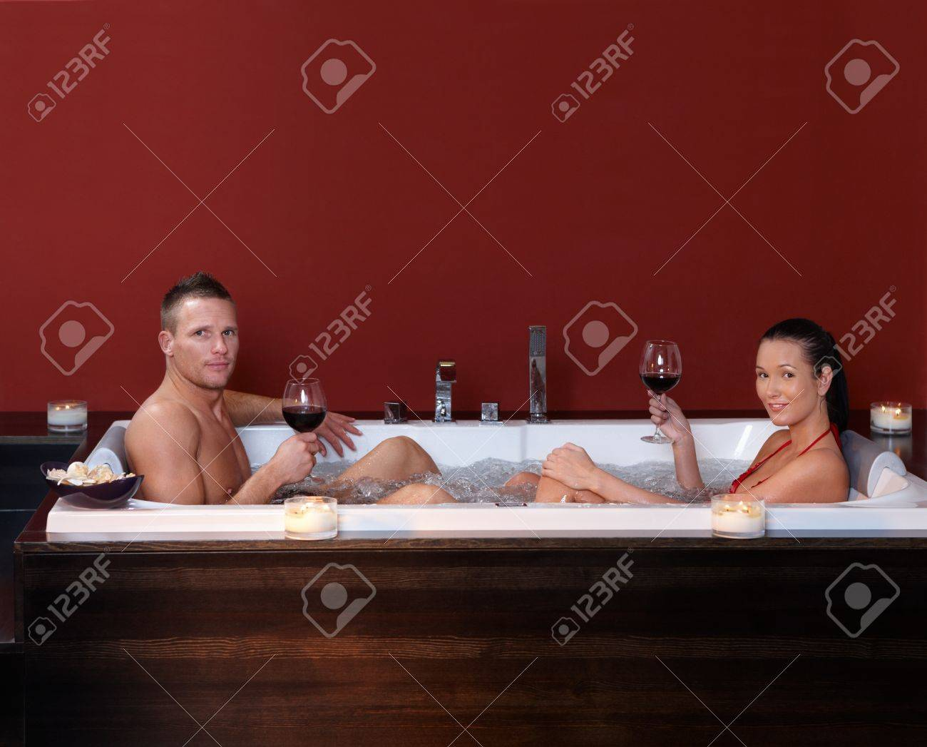 Couple sitting in bubble bath, having red wine in wellness environment, looking at camera. Stock Photo - 8752646