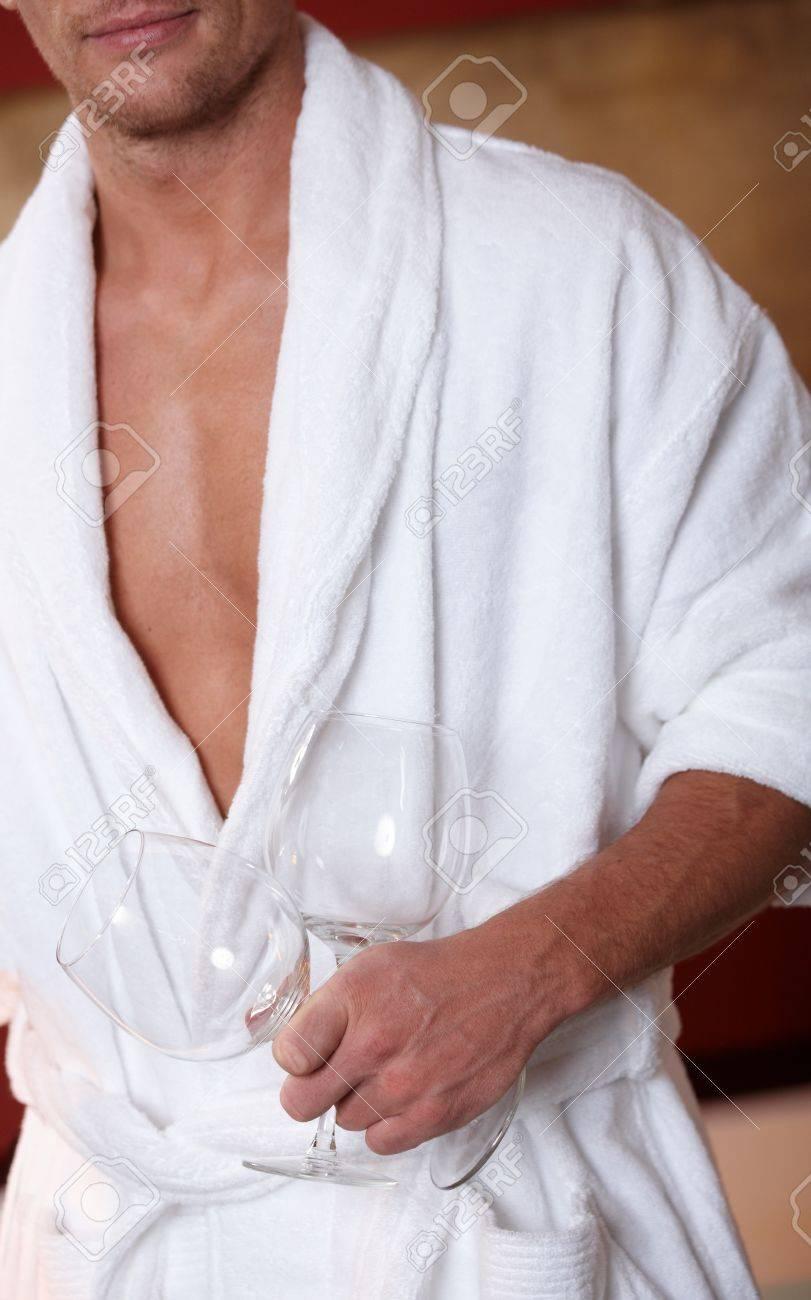 Sporty man in bathrobe holding wine glasses. Stock Photo - 8753322