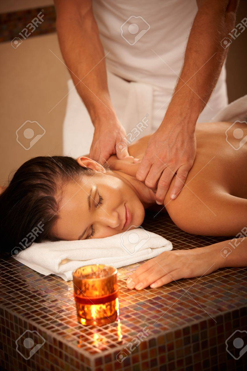 Young woman enjoying massage with eyes closed in wellness environment. Stock Photo - 8753406