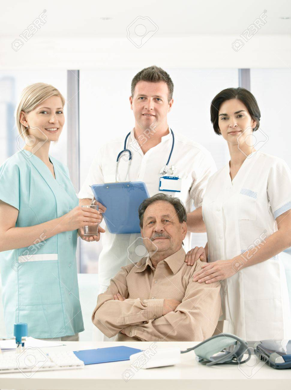 Portrait of senior patient sitting surrounded with medical crew, looking at camera, smiling. Stock Photo - 8782938