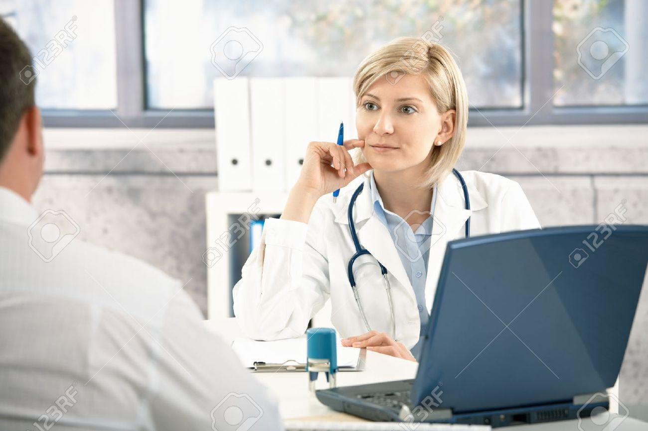 Doctor listening to patient with concentration, sitting at desk in office. Stock Photo - 8782896