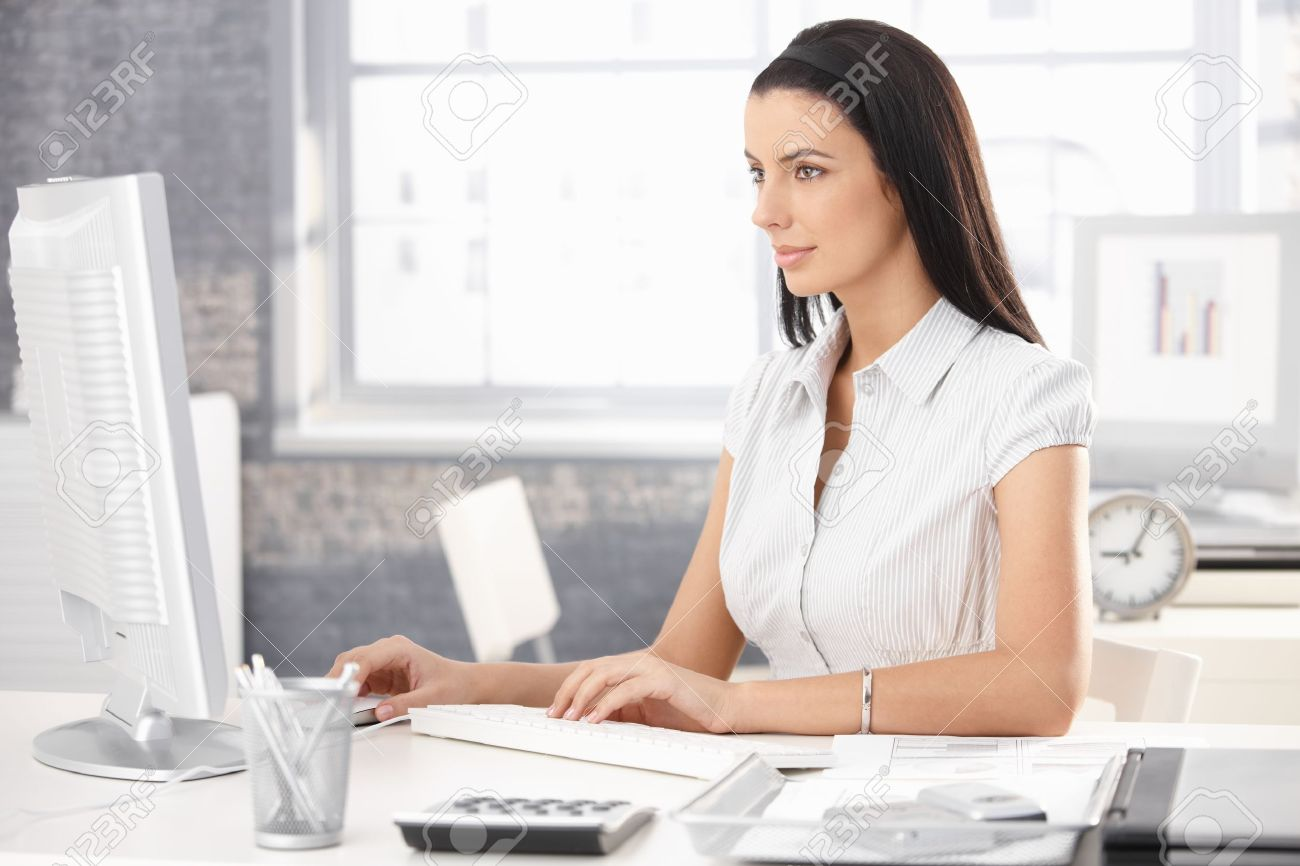 Pretty office worker girl sitting at desk in office, using desktop computer. Stock Photo - 8782775