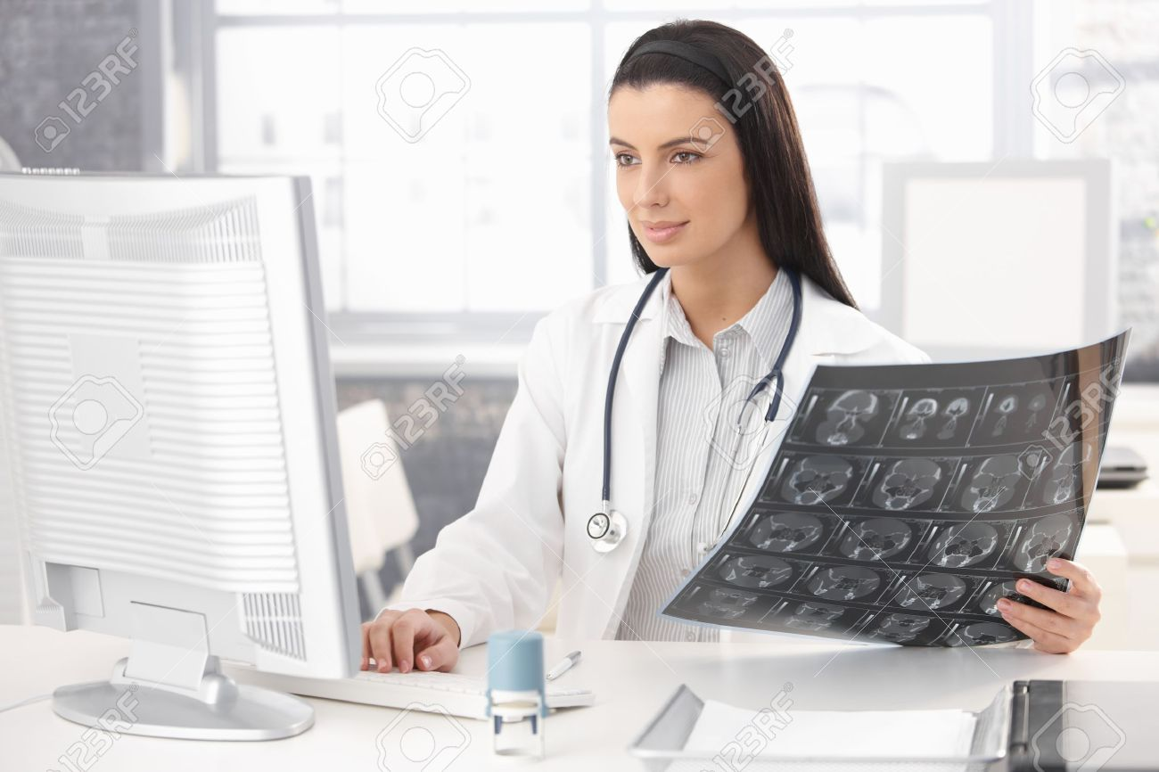 Smiling doctor sitting in office working at desk with computer and xray image. Stock Photo - 8782763