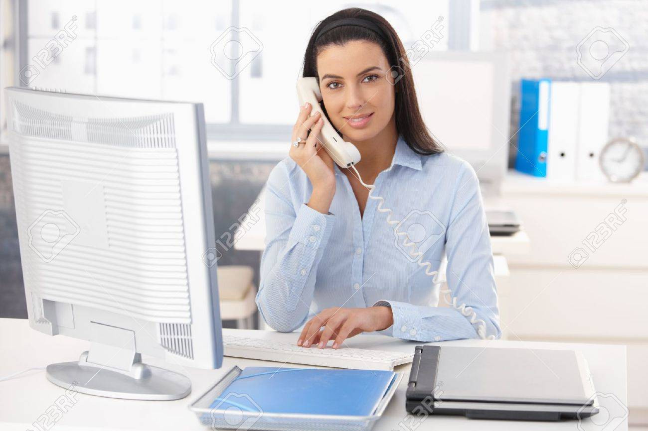 Portrait of smiling woman working in office, using computer and landline phone. Stock Photo - 8782766