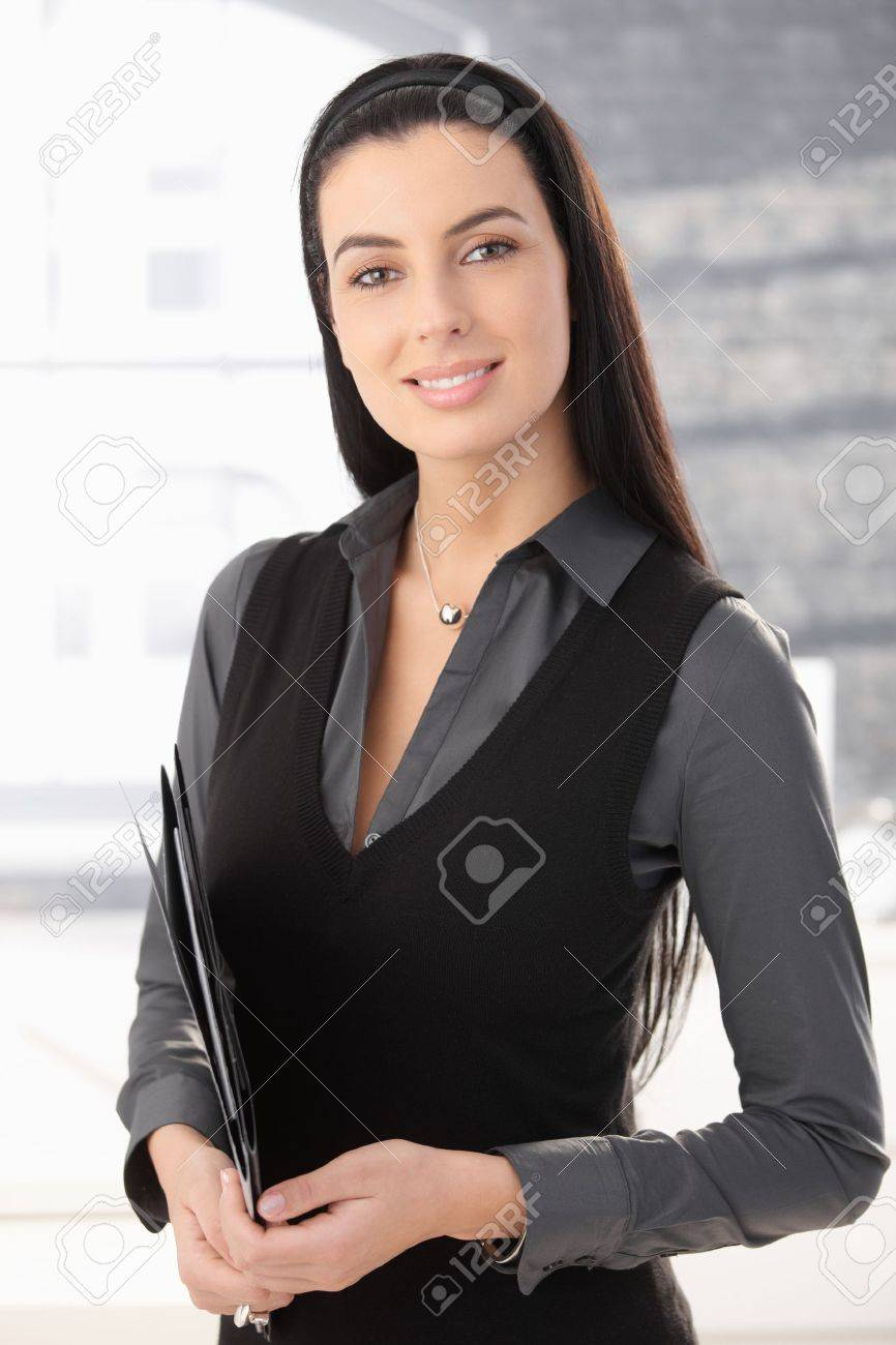Portrait of smart office worker woman standing in office with document folder, smiling. Stock Photo - 8783075