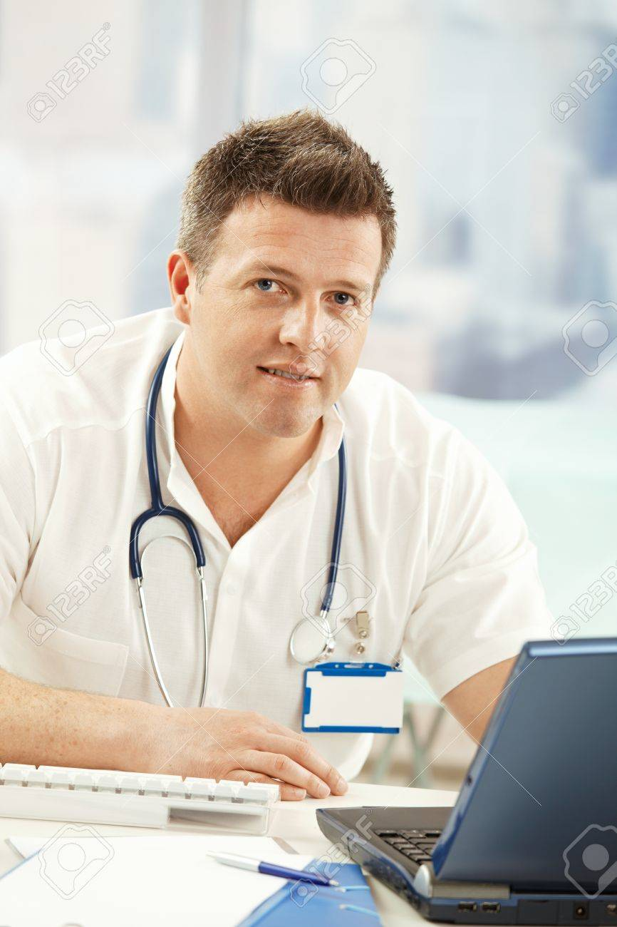 Portrait of confident doctor smiling at camera sitting at desk with computer. Stock Photo - 8783229