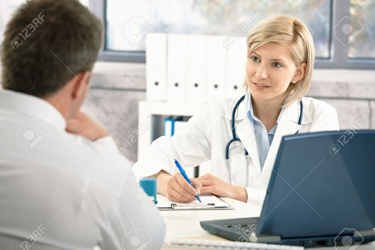 Doctor talking to patient in office, taking notes, smiling. Stock Photo - 8782897