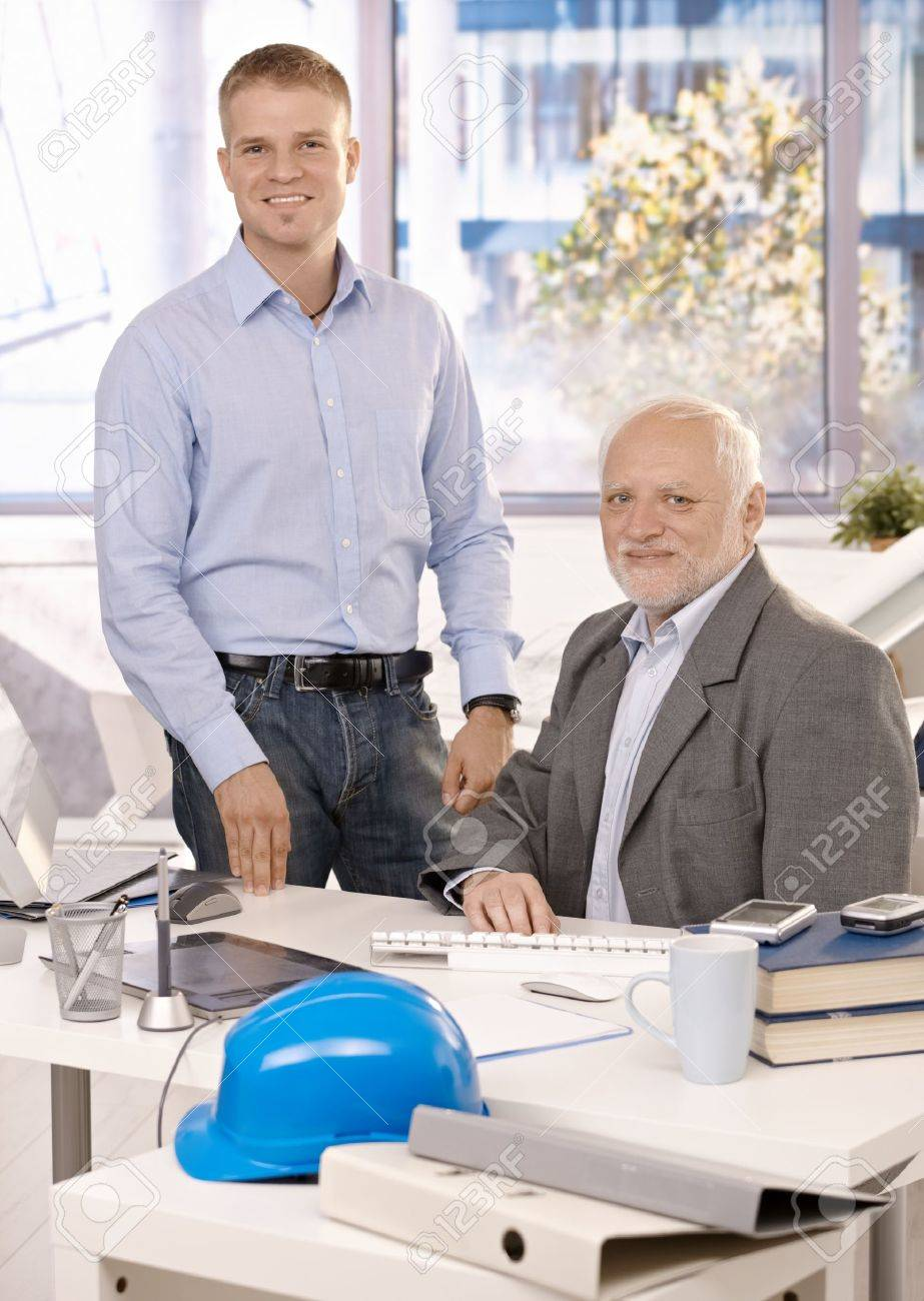 Portrait of senior and junior businessmen working in office, looking at camera, smiling. Stock Photo - 8783541