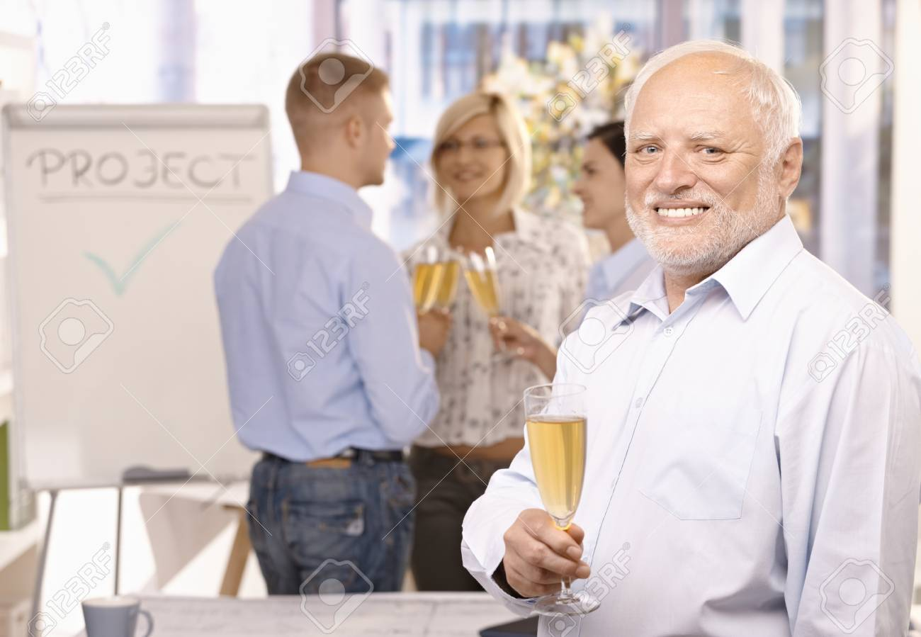 Portrait of senior businessman celebrating project done in office with champagne, employees talking in background. Stock Photo - 8783383