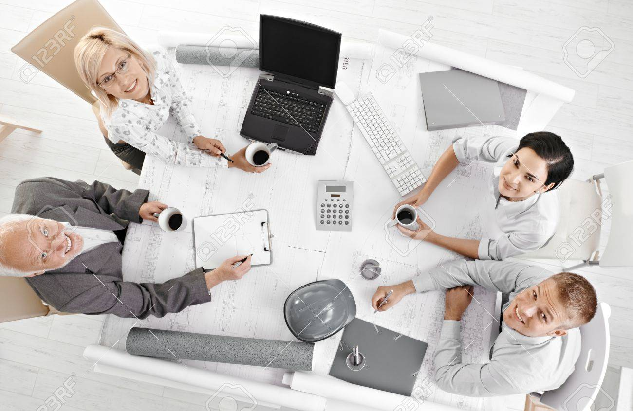 Portrait of business meeting, coworkers looking at camera from high angle view, smiling. Stock Photo - 8783384