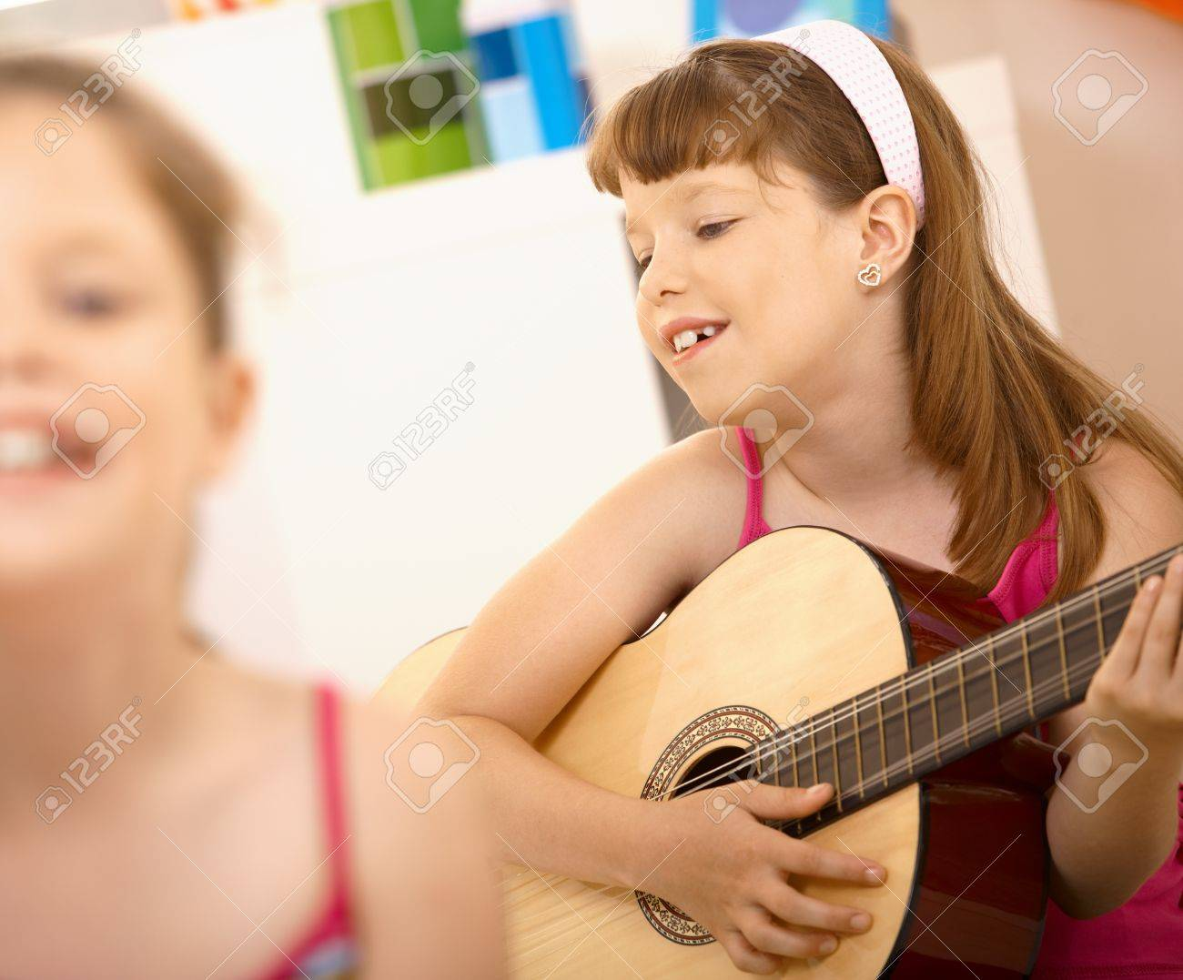Young girl enjoying playing guitar, smiling at home. Stock Photo - 8783916