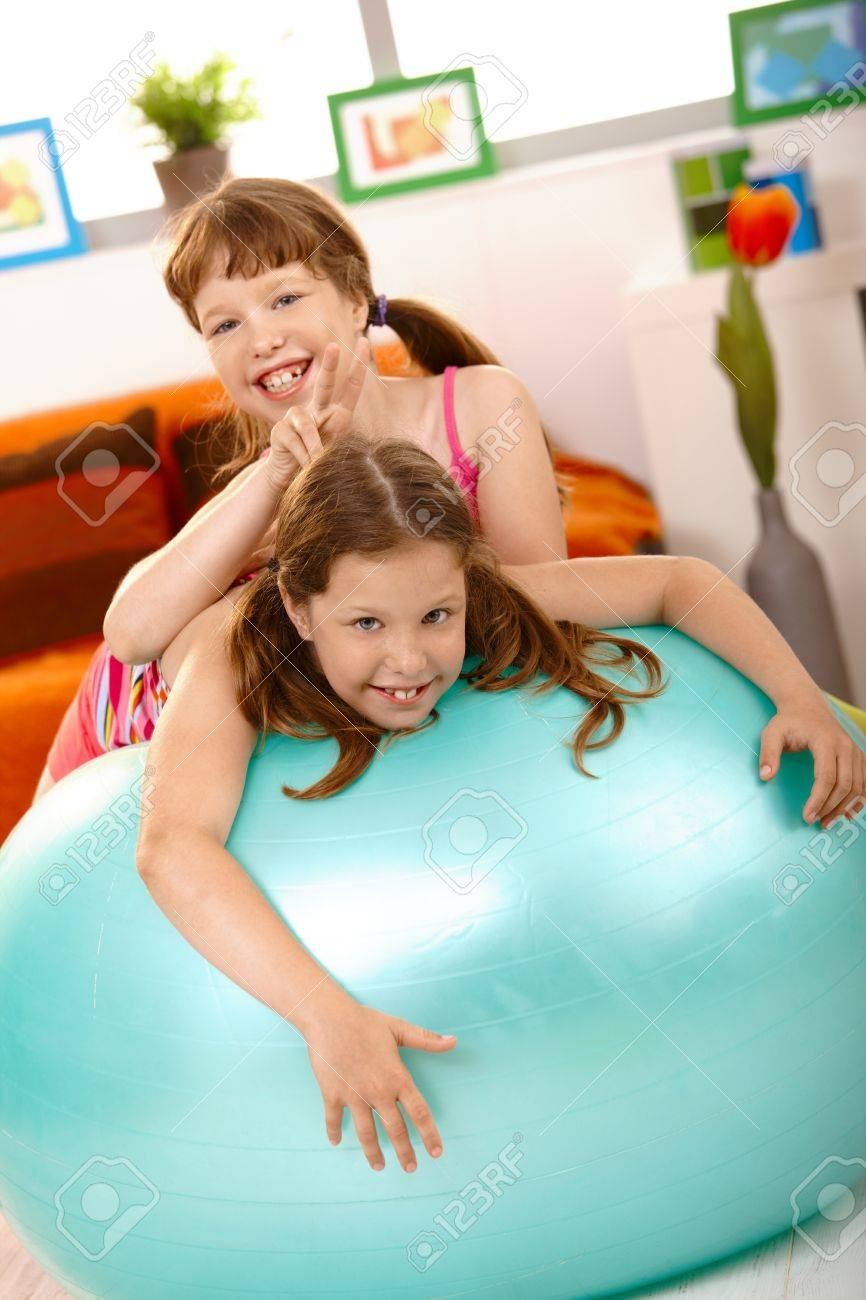 Schoolgirl teasing friend on gym ball, showing dog's-ear, laughing. Stock Photo - 8784220