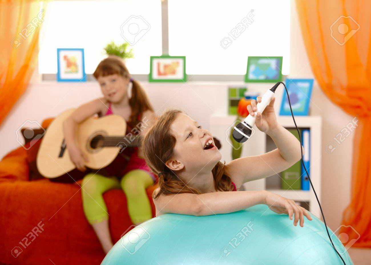 Young girl singing into microphone, having fun with guitar player friend at home. Stock Photo - 8783878