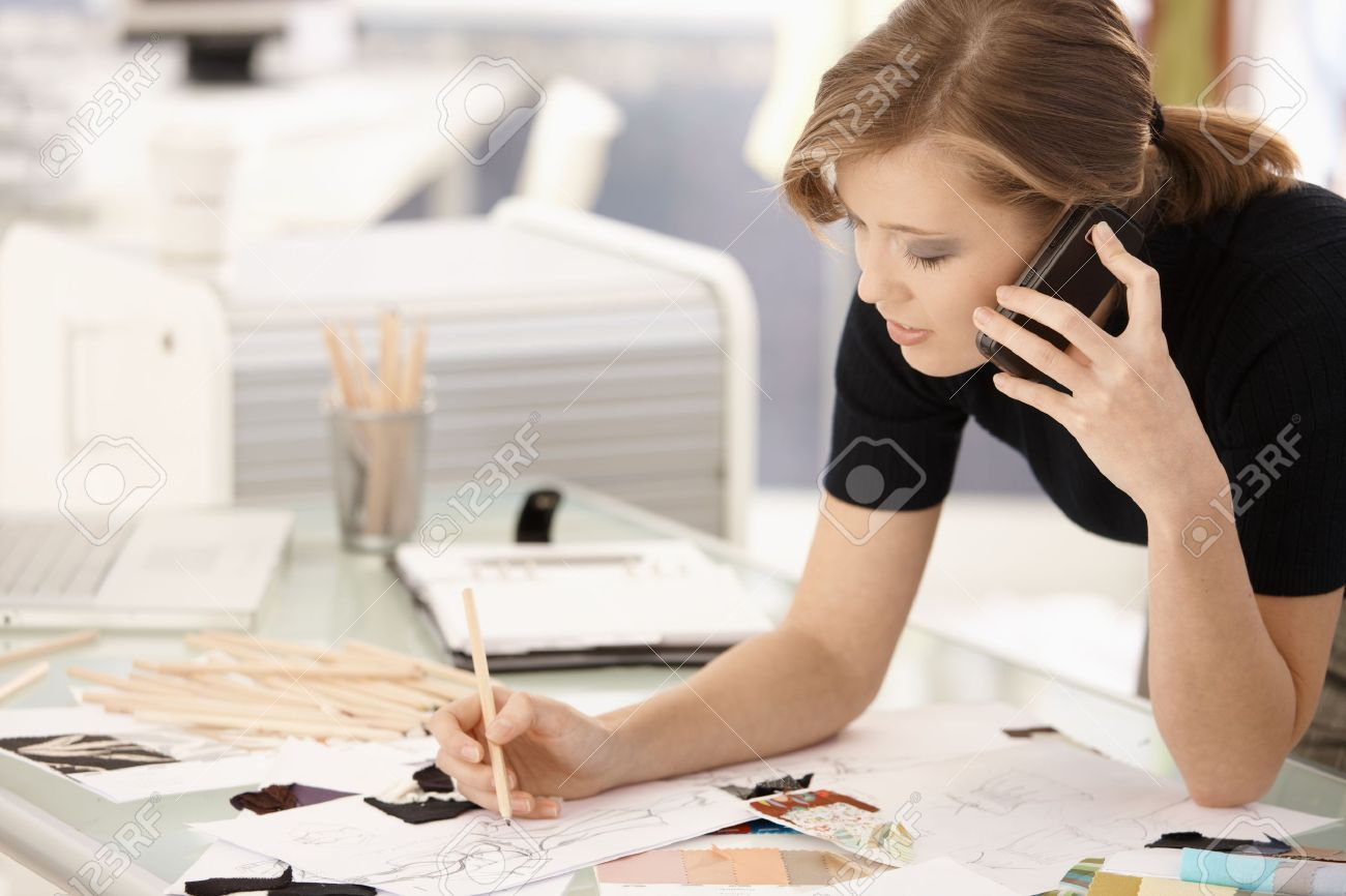 Young attractive female fashion designer working at office desk, drawing while talking on mobile. Stock Photo - 8784138