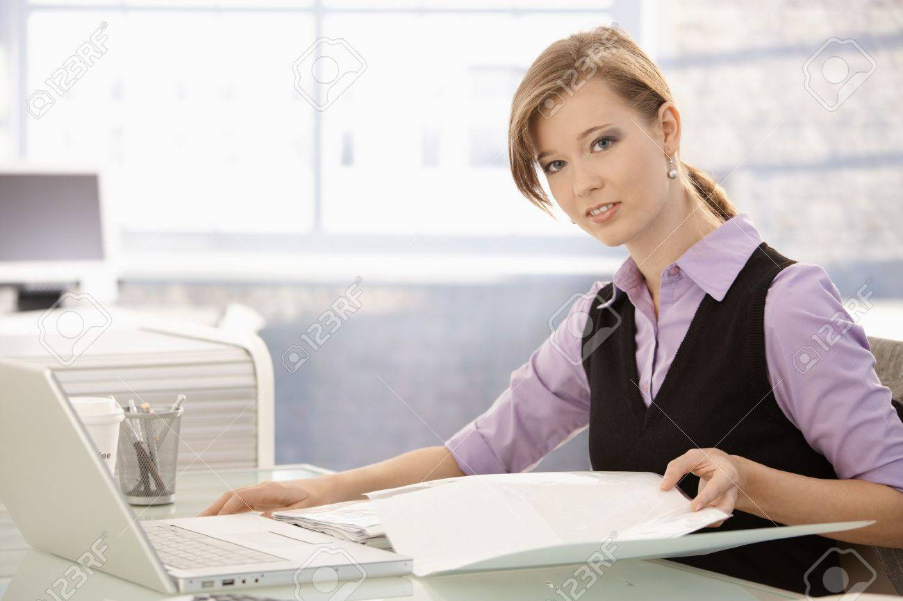 Office worker sitting at desk, doing paperwork. Looking at camera, smiling. Stock Photo - 8784016