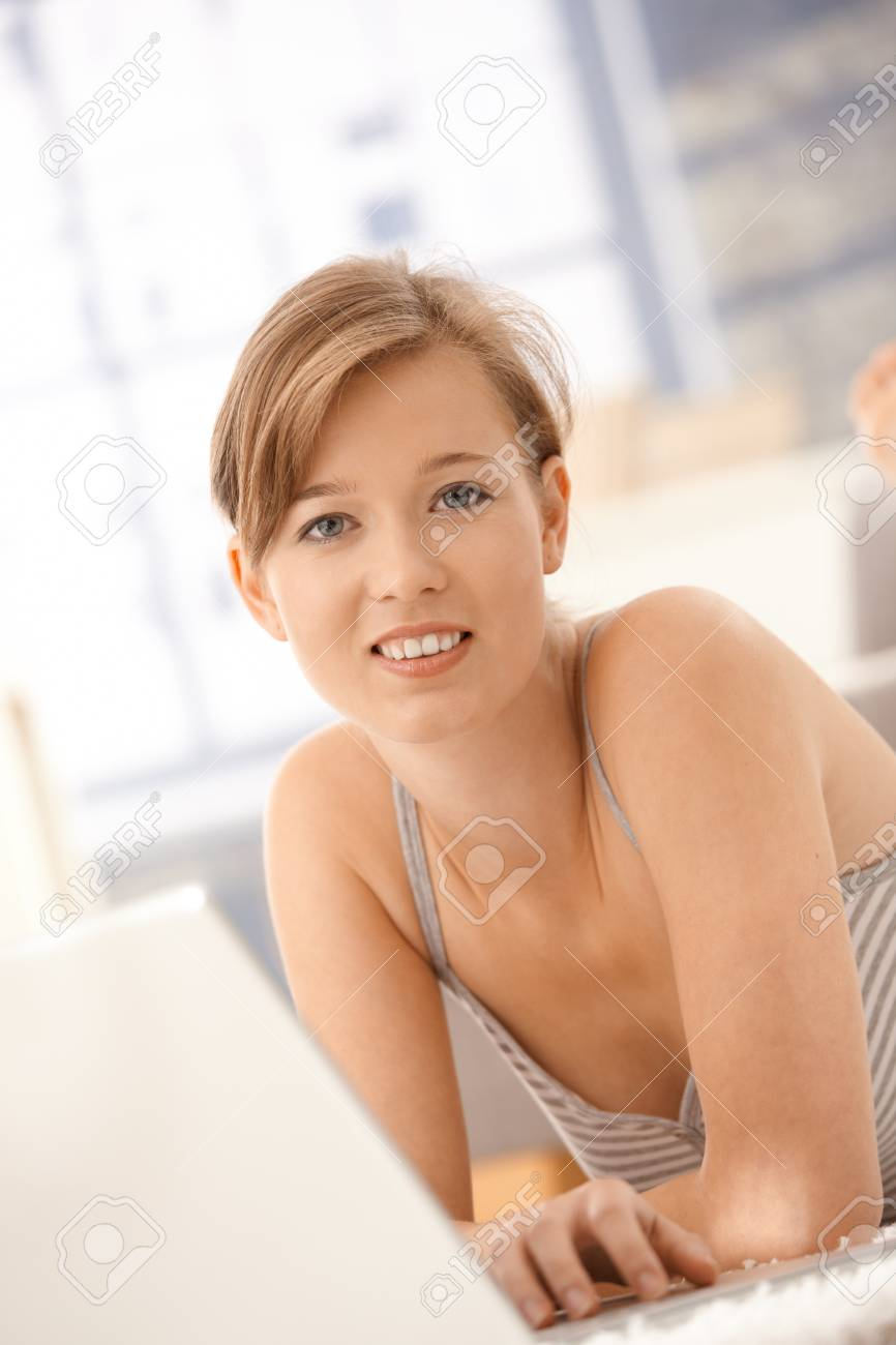 Closeup portrait of happy young woman using laptop computer at home. Looking at camera, smiling. Stock Photo - 8783911