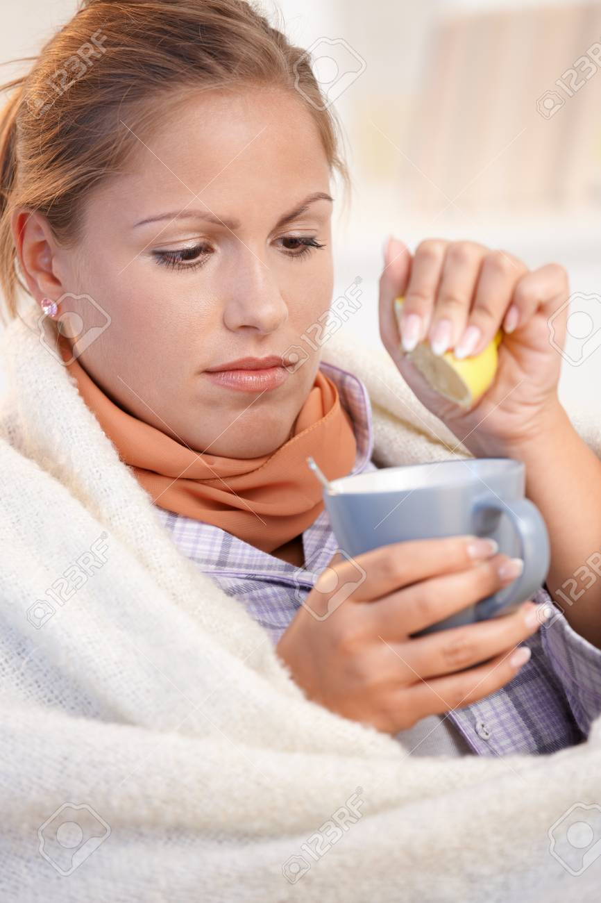 Young female caught cold, feeling bad, wrapped up in blanket, squeezing lemon to her tea. Stock Photo - 8908725
