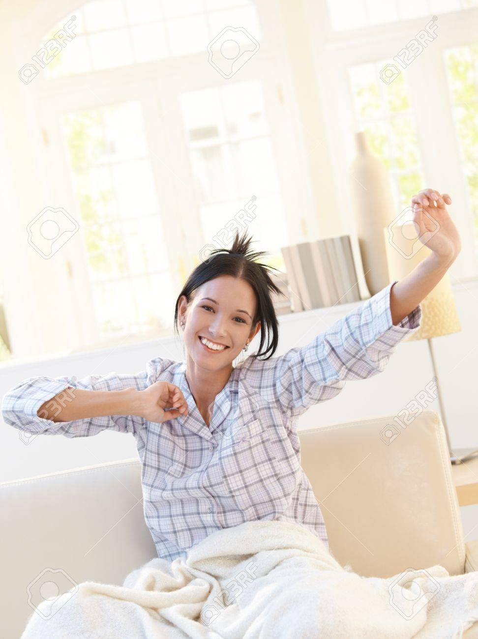 Happy attractive woman stretching in pyjama on sofa in bright living room, smiling at camera. Stock Photo - 8908490