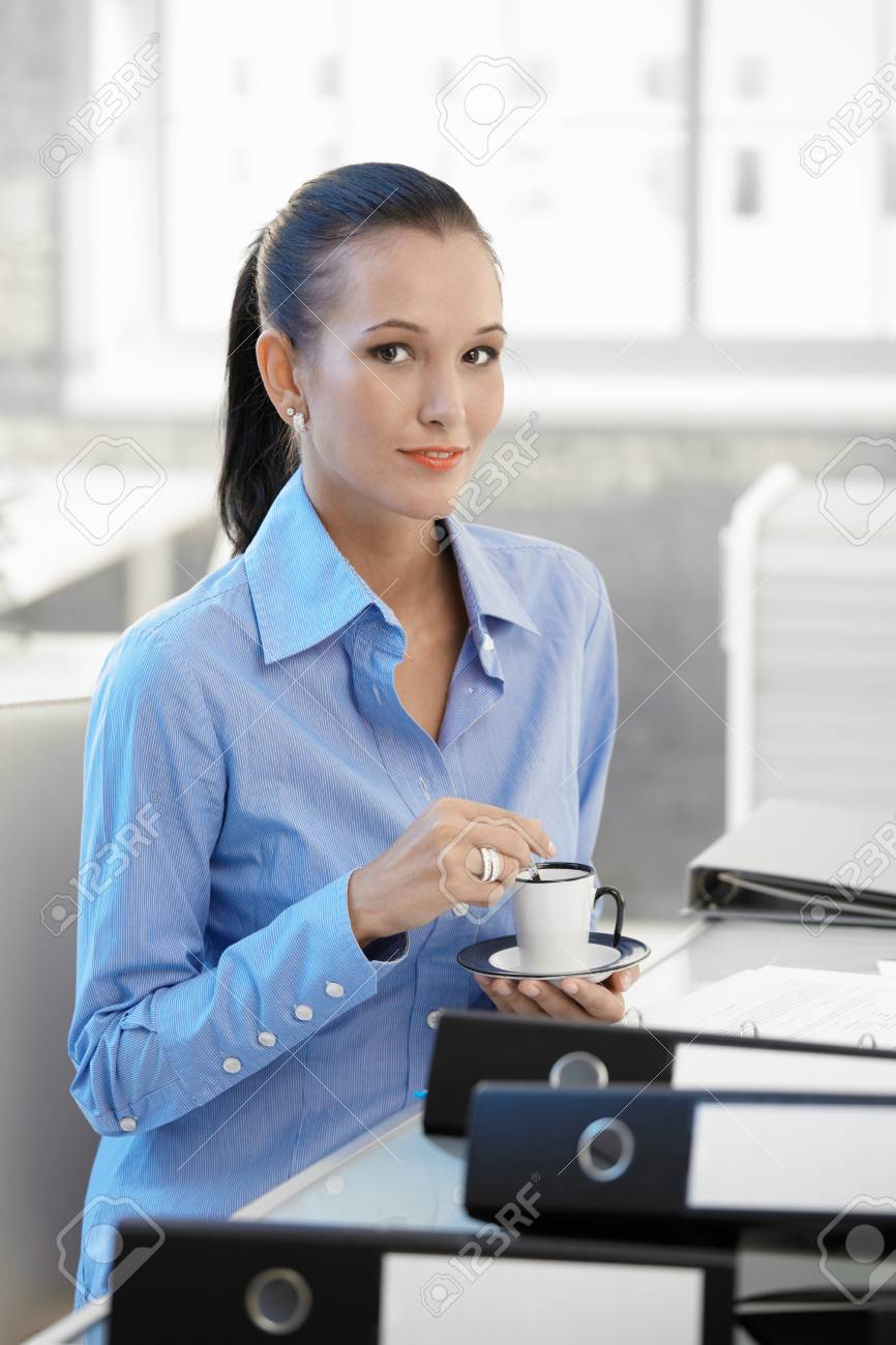 Smiling office worker girl having coffee, sitting at desk, looking at camera. Stock Photo - 8896076