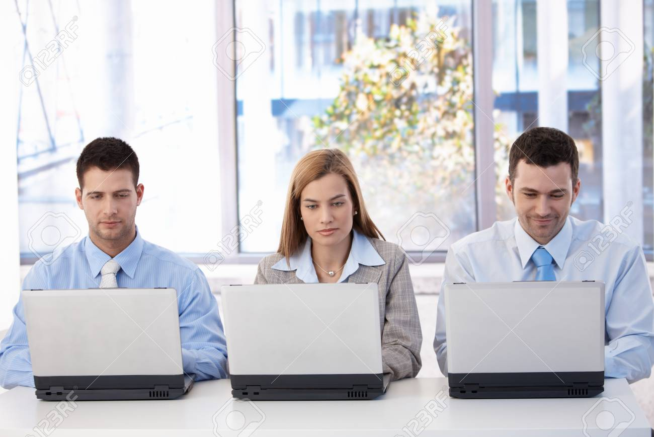 Young businesspeople sitting at desk in bright office, busy by working on laptop. Stock Photo - 8951296