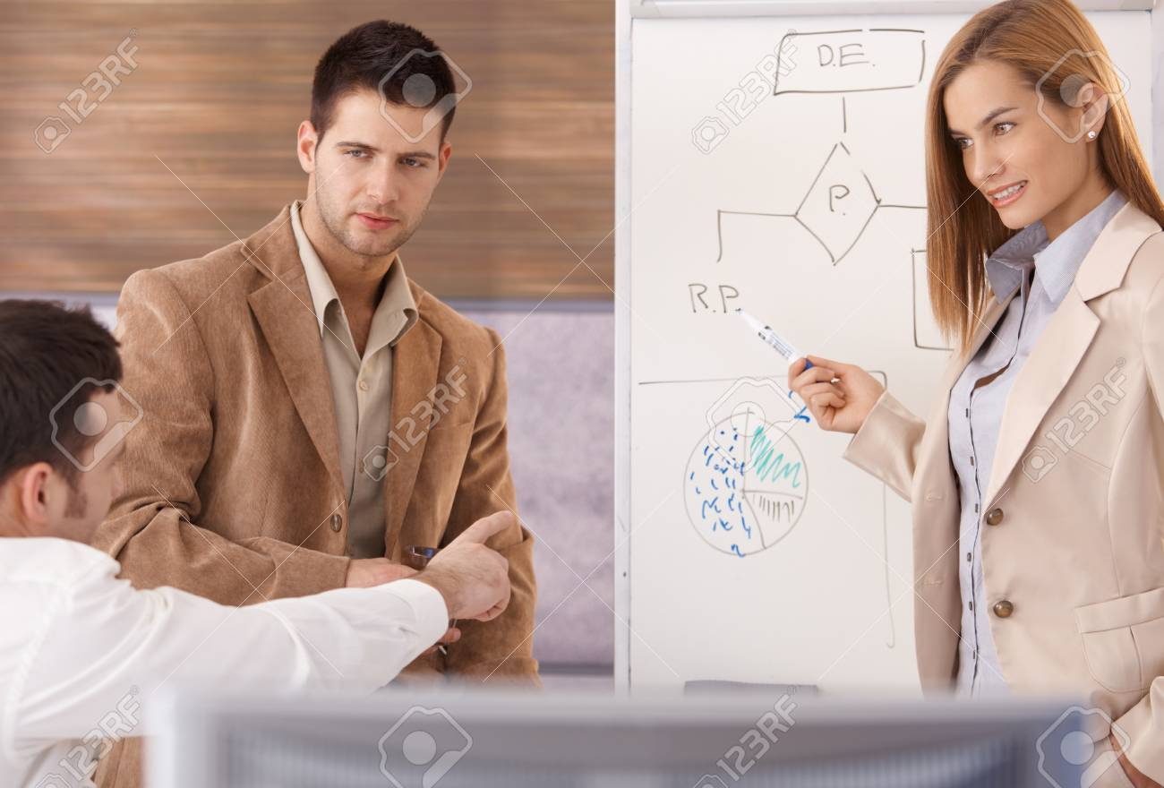 Young businesspeople teamworking with whiteboard, woman presenting, smiling. - 8951257