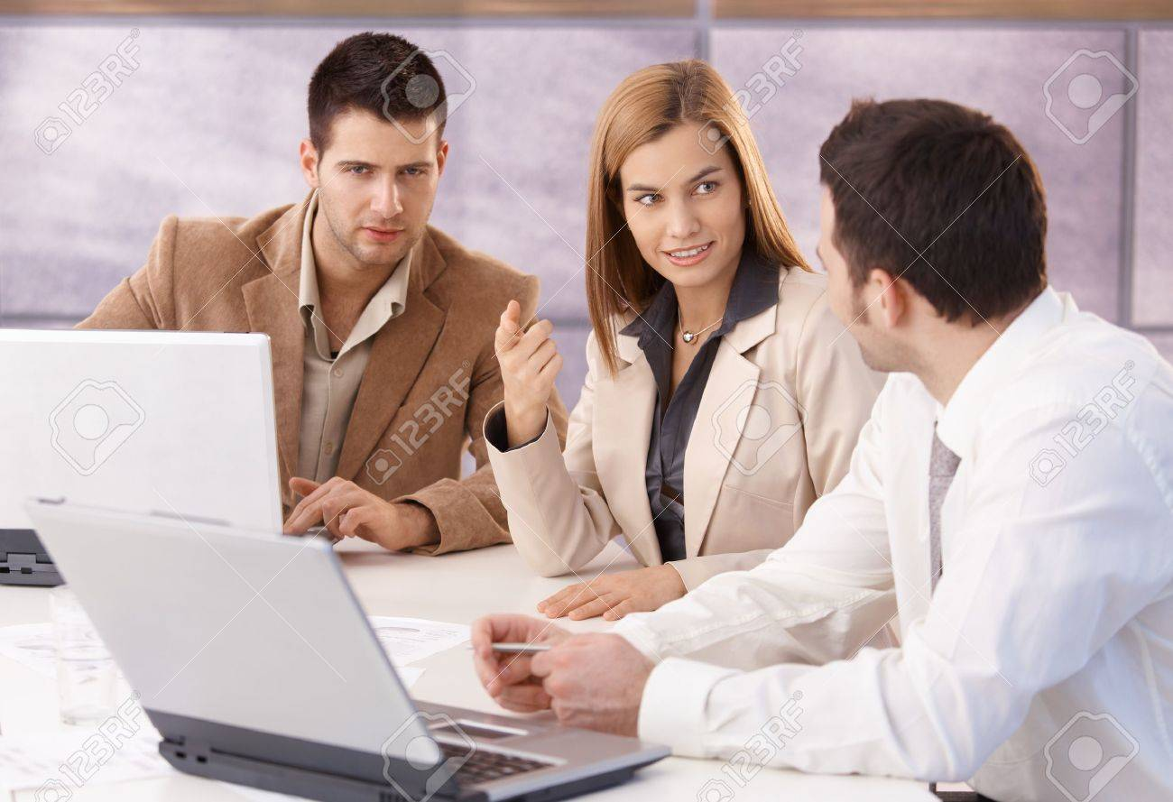 Young professionals teamworking in meeting room, smiling. Stock Photo - 8951262
