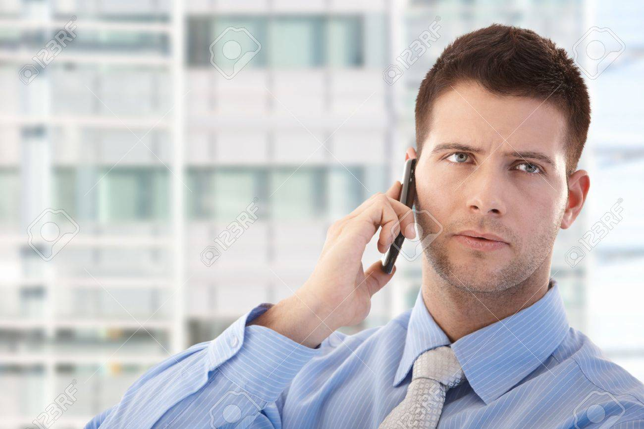 Handsome young businessman using mobile phone in modern office front of window. Stock Photo - 9066115