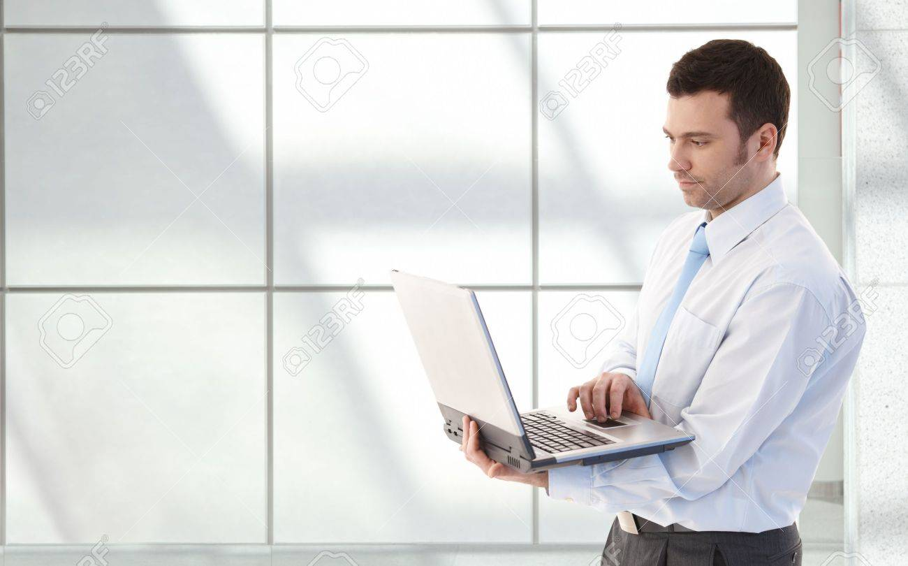 Young businessman working on laptop, standing in office lobby. Stock Photo - 9066123
