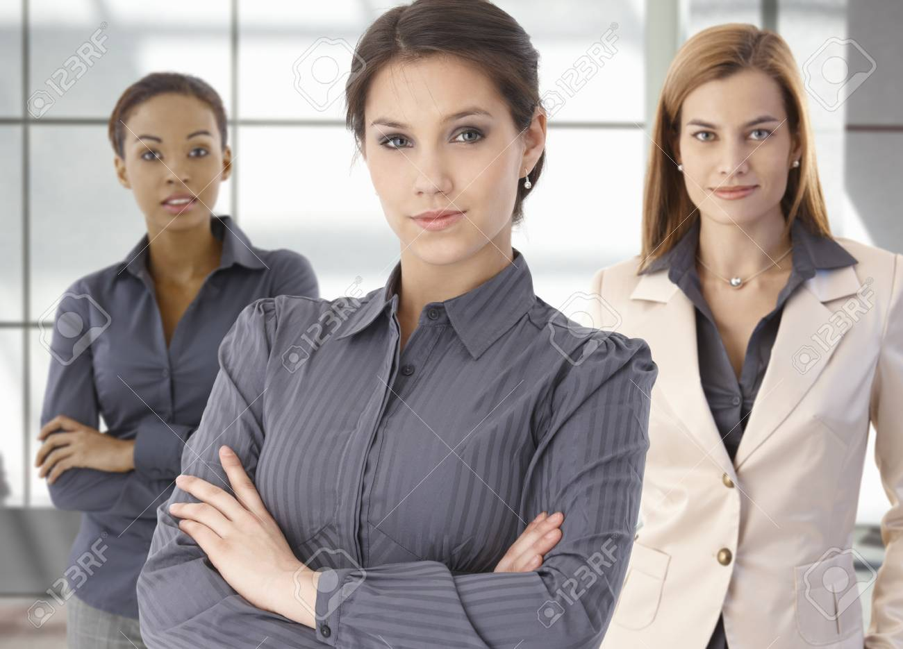 Team portrait of happy businesswomen standing on office corridor, looking at camera, smiling. Stock Photo - 9066312
