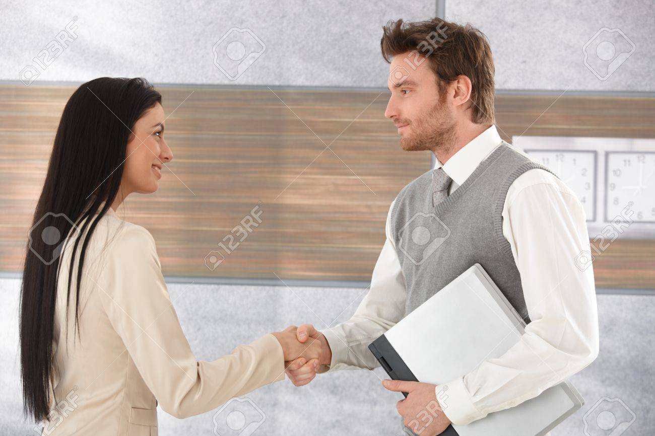 Young businesspeople greeting each other by shaking hands smiling stock photo young businesspeople greeting each other by shaking hands smiling m4hsunfo