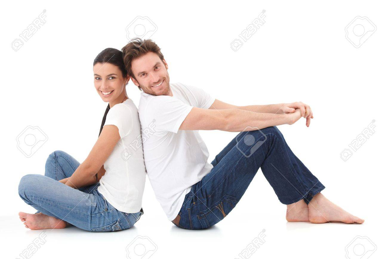 Cheerful young couple sitting with back to each other on floor, smiling happily. Stock Photo - 9201681