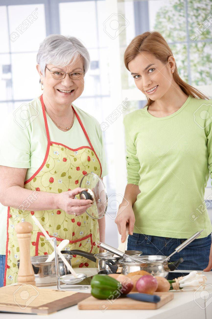 Senior mother and attractive daughter cooking together in kitchen, smiling. Stock Photo - 9209315
